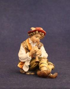 Pastore seduto con piffero la statuina in legno del presepe tradizionale