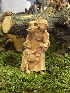 Statuina del presepe della pastorella con bimbo e pane nella variante naturale